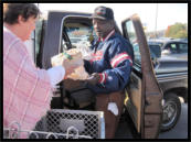 A volunteer helps a recipient put food into his truck.