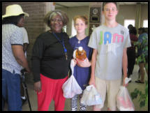 Two young volunteers help a client out with her groceries.