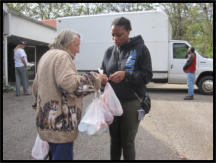 A volunteer helps a recipient with her groceries.