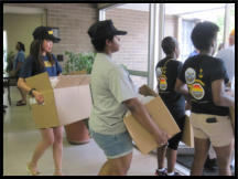 Navy Shipmates carry boxes out for delivery to our oldest clients.